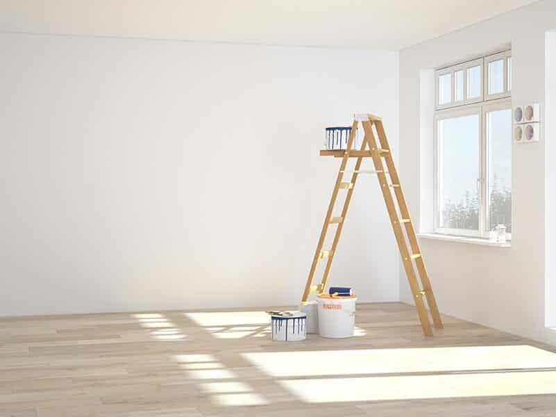 Ein frisch gestrichener Raum nach einer Entrümpelung und Renovierung mit Leiter und Farbeimer
