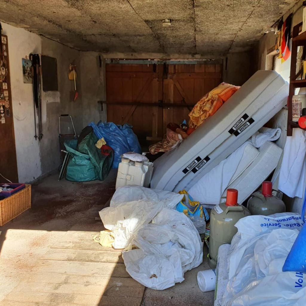 Zugemüllte Garage mit Abfällen vor einer Entrümpelung in Berlin-Brandenburg